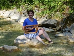 Sie sehen die Klangtherapeutin mit einem Treveller-Didgeridoo auf einem großen Stein inmitten der Pöllat.