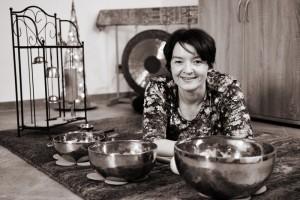 Annette Rentema liegt zwischen ihren tibetischen Klangschalen und blickt lächelnd in die Kamera.