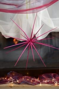 Ein pink-glitzernder Stern vor dem weihnachtlich geschmückten Terrassenfenster.
