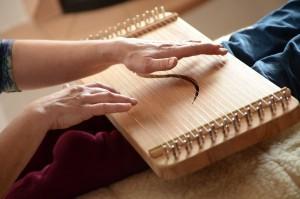 Ein Behandlungsmonochord liegt auf den Unterschenkeln eines Menschen und wird zur Massage gespielt