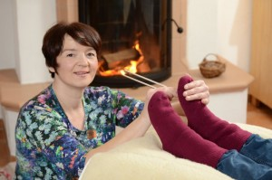 Annette Rentema blickt in die Kamera während sie eine Planetenton-Stimmgabel an die Fußsohle eines liegenden Menschen hält