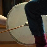 Ein Bein wird mit der Schamanentrommel behandelt.