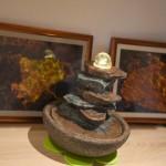 Ein Zimmerbrunnen, bei dem sich eine Kristallkugel auf aufgeschichteten flachen Steinen dreht